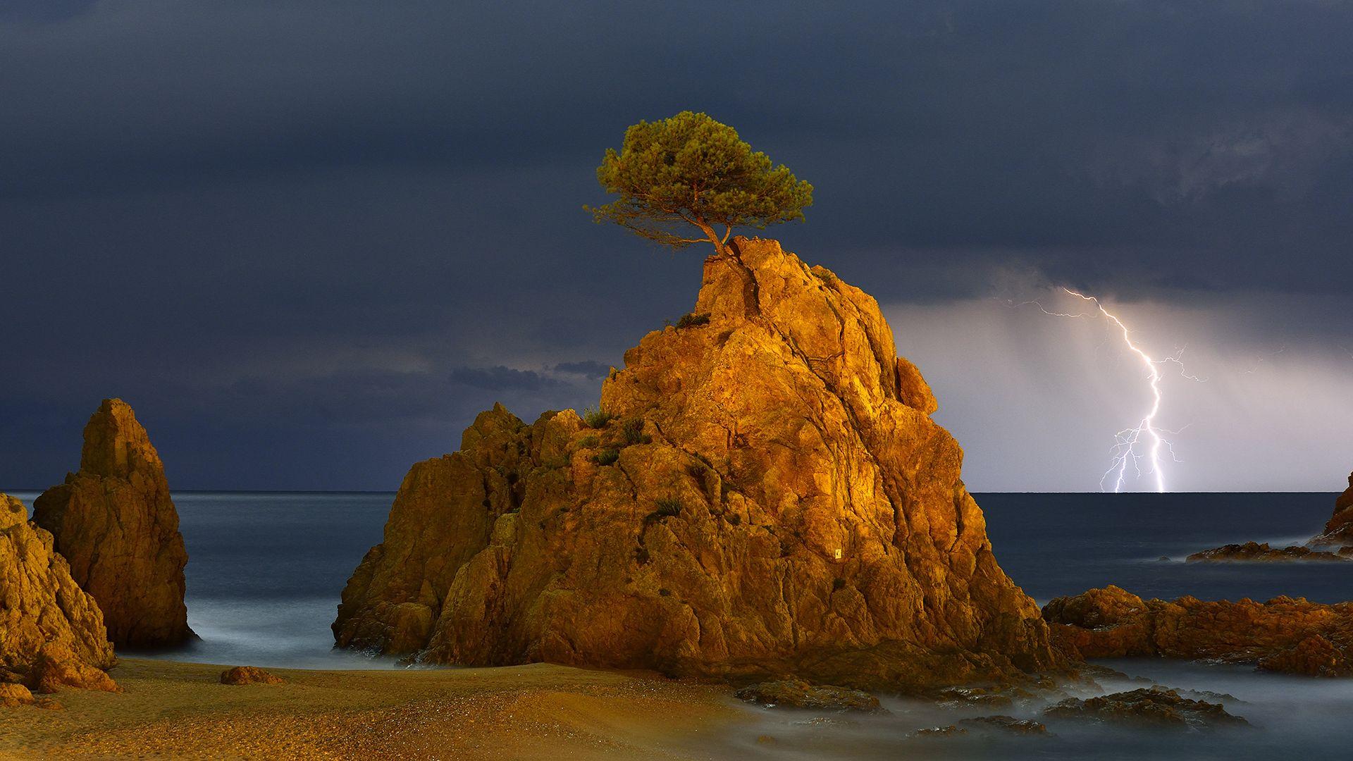 Pine rock lightning and full moon